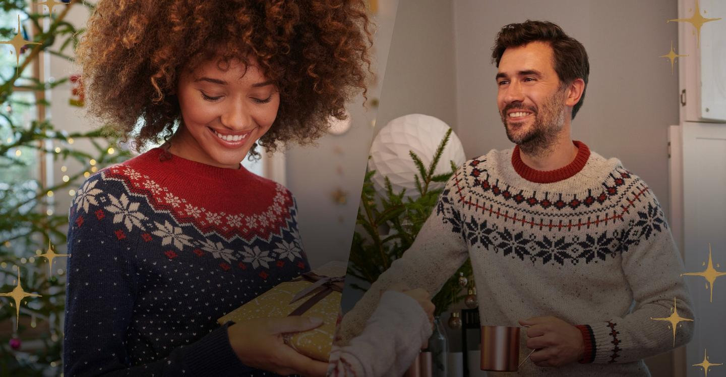 Female model wearing a navy and red fairisle jumper next to a male model wearing an ivory fairisle jumper by a christmas tree.