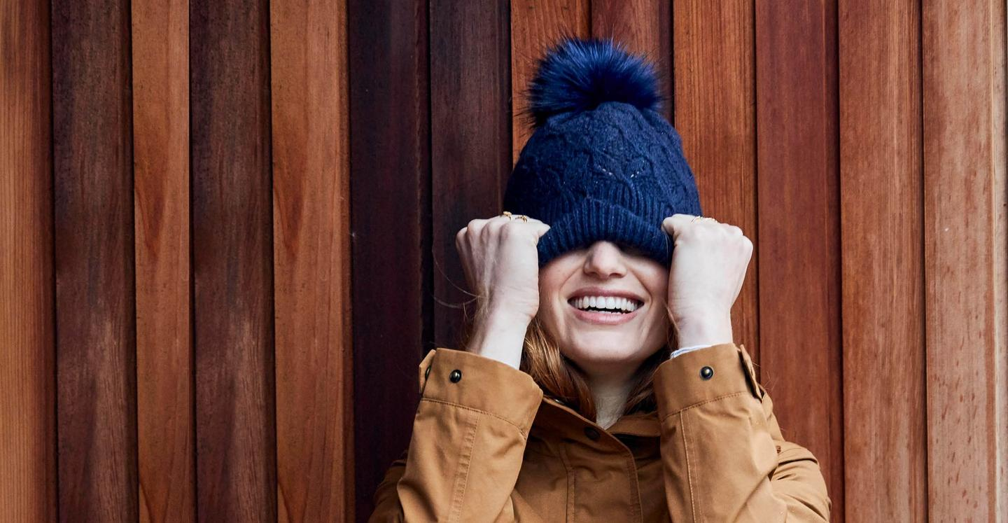 Shot of a female Fatface model wearing a brown jacket with a navy bobble hat - stood infront of a wooden background.