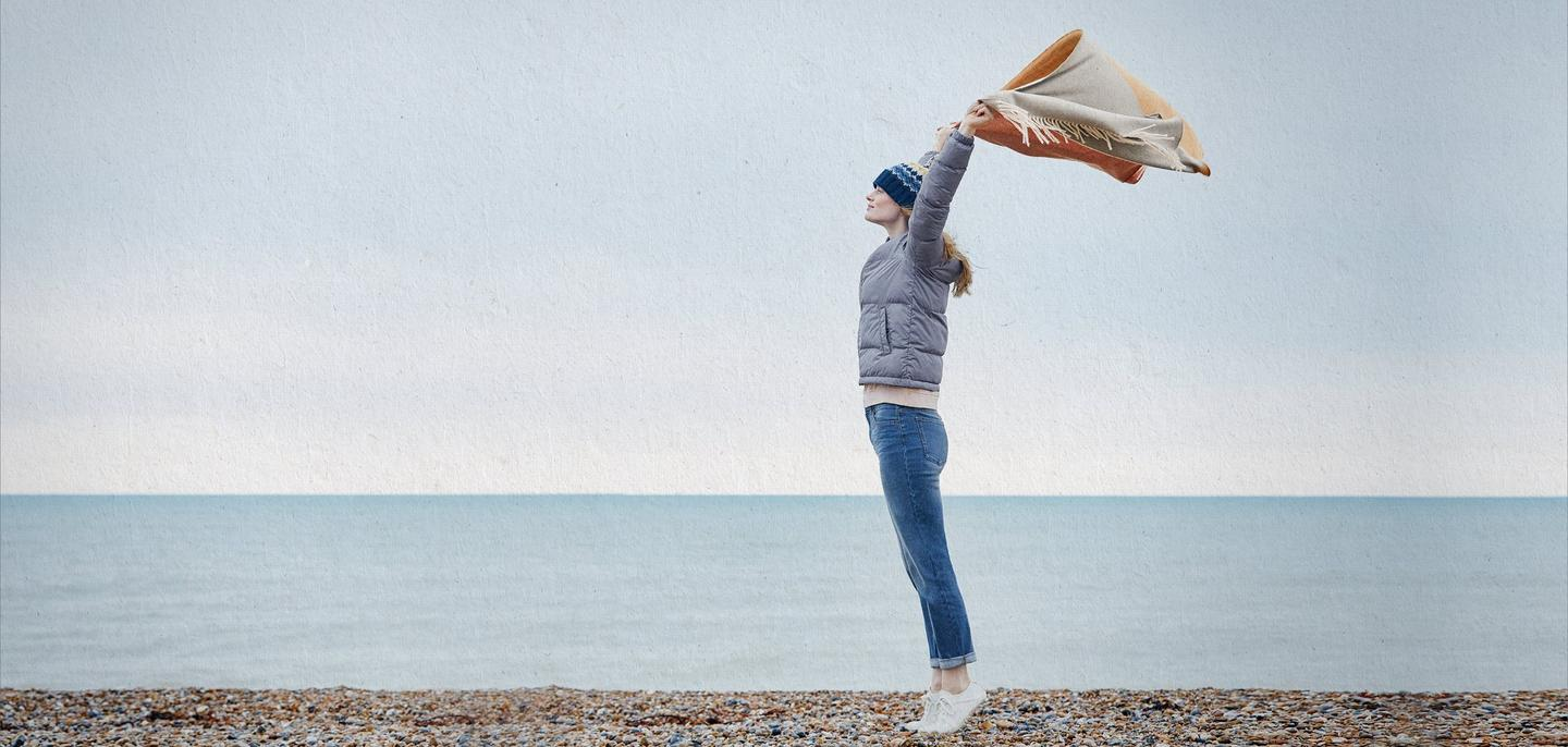 A woman standing on a pebble beach, wearing a coat and jeans while holding a scarf in the air.