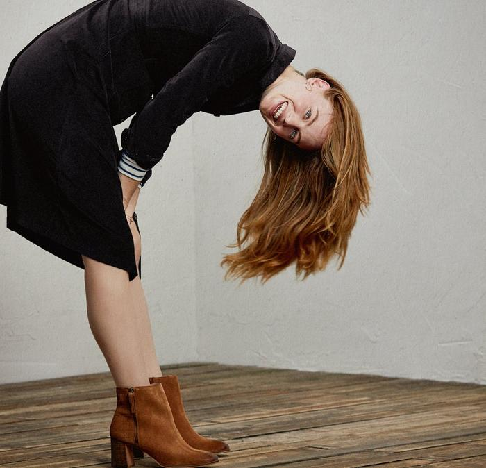 A woman wearing a cord dress and ankle boots, playfully bending over.