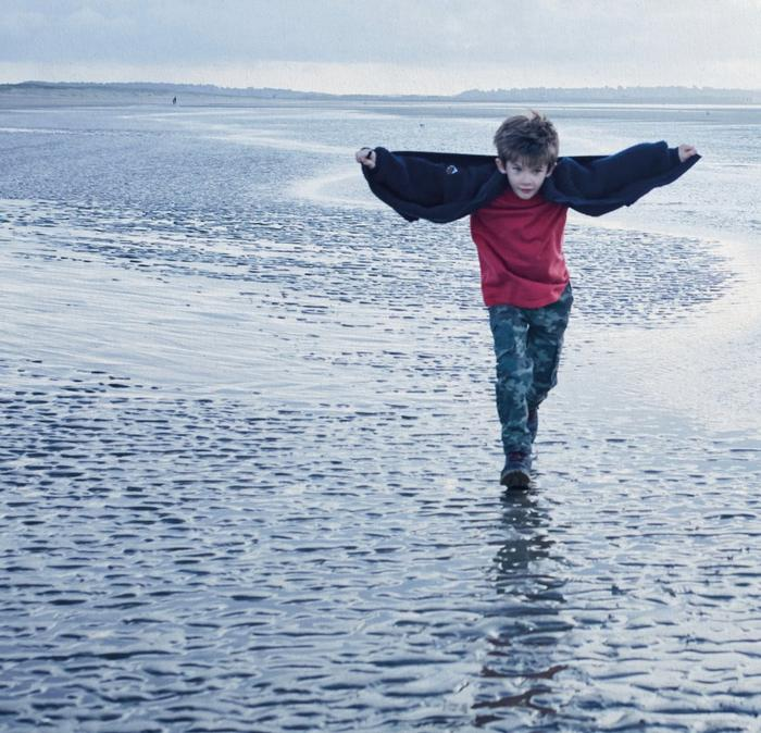 A young boy playfully running along the beach, his jacket open like a cape.