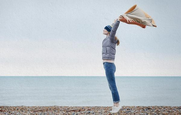 A woman on a pebbled beach, wearing warm winter clothes and sustainable sneakers.