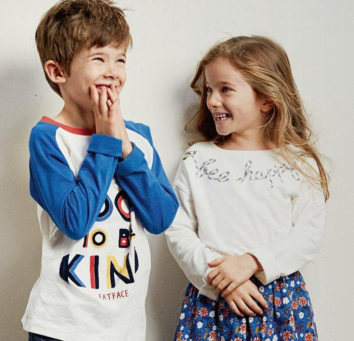 Boy wearing 'It's cool to be kind' long sleeved graphic tee. Girl wearing a 'Bee happy' embroidered top & floral print skirt.