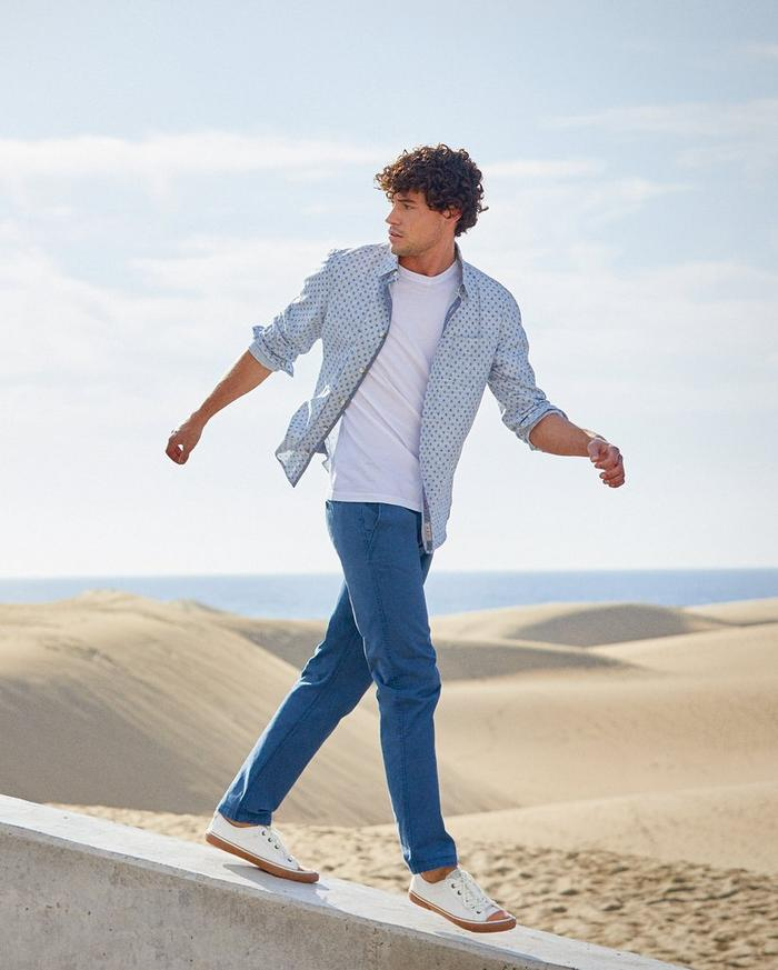 Male model wearing a blue geo print long sleeve shirt with blue chinos walking in the sand.