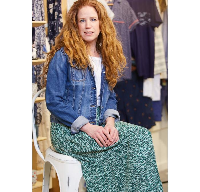 Rachel, Senior Accessories Buyer, wears a denim jacket with a green printed maxi skirt.