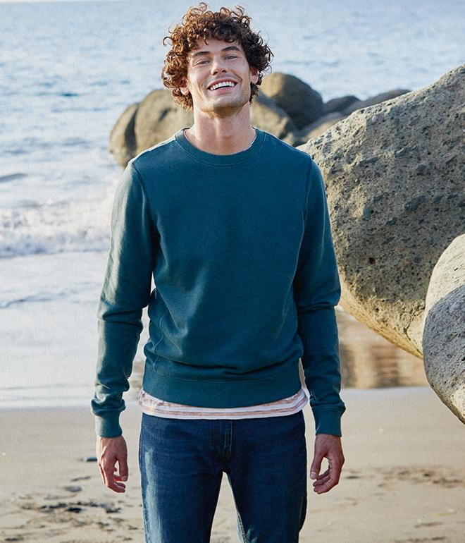 Male model on the beach wearing a dark green crew neck sweatshirt and jeans.
