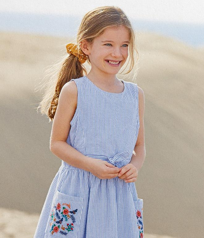 Girl model wearing a blue and white pin stripe summer dress, with her hair tied with a yellow scrunchie.