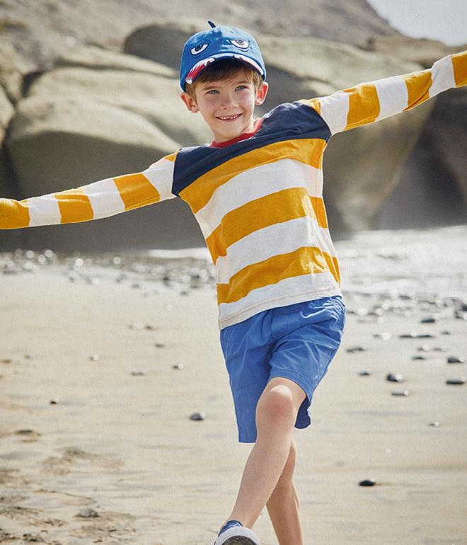 Boy model on the beach wearing a yellow and white stripe long sleeve tee, blue shorts and a shark baseball cap.