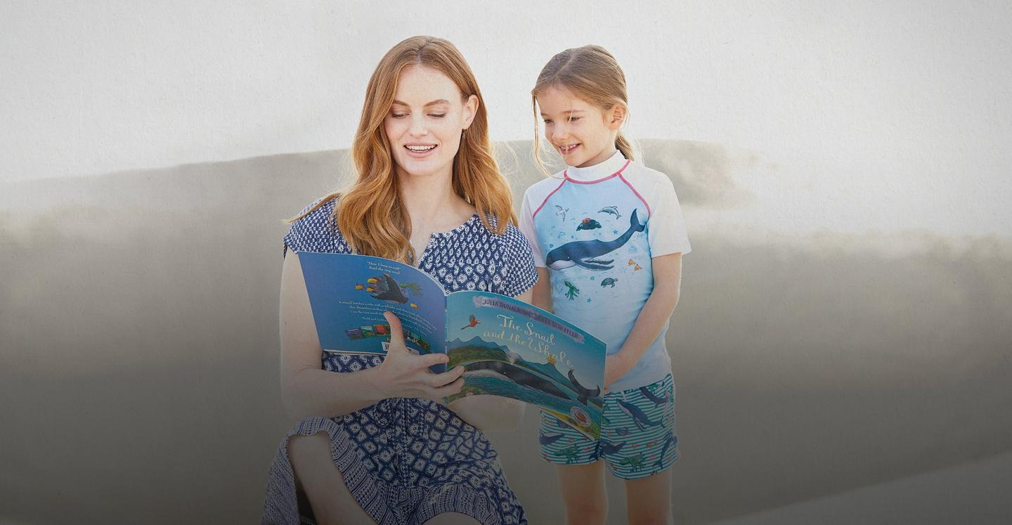 A female model in a blue geo tile dress reading The Snail and the Whale with a girl model in a rash vest and swim shorts.