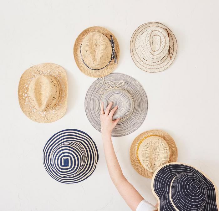 A selection of summer straw hats hanging on a wall with a woman reaching up to them.