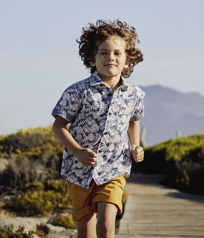 Boy model wearing a white palm print shirt with yellow shorts.