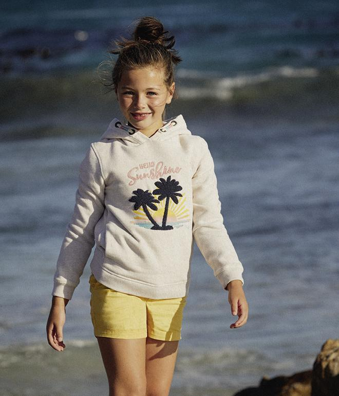 Girl model wearing an ivory hoody with a palm print graphic.