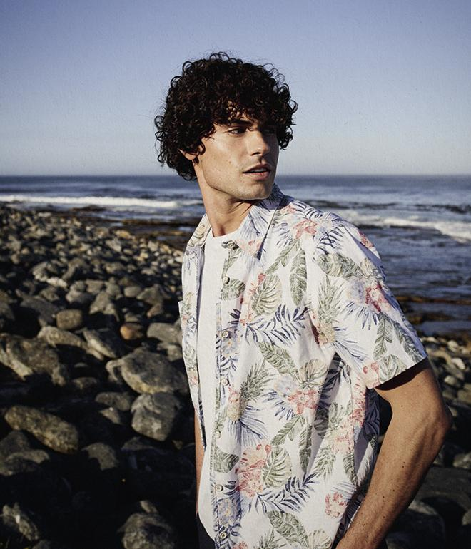 Male model wearing a blue and white Hawaiian floral shirt over a white t-shirt.