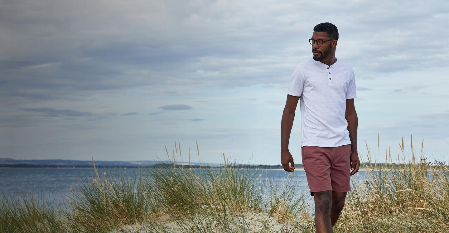 A male model standing on a coastal path, wearing a white button-neck t-shirt & reddish chino shorts.