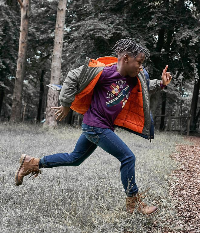 Boy running through a forest wearing a purple graphic t-shirt and a khaki parka coat.