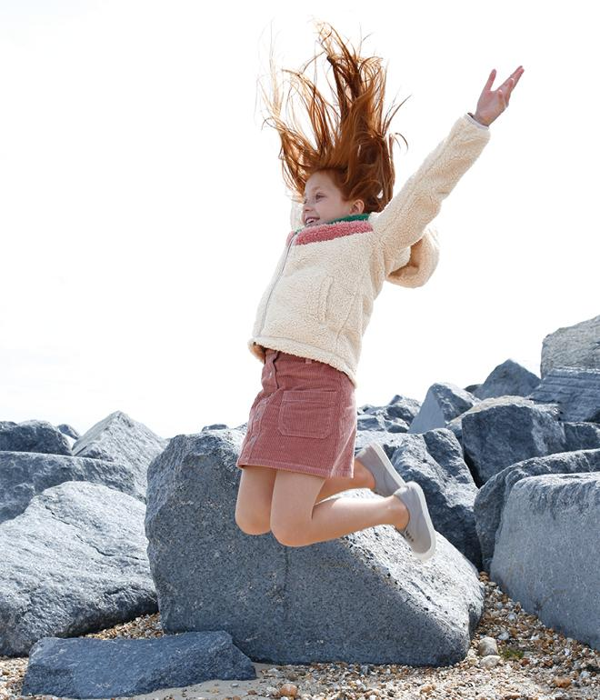 Girl jumping in the air wearing a white borg fleece hoody and pink cord skirt.