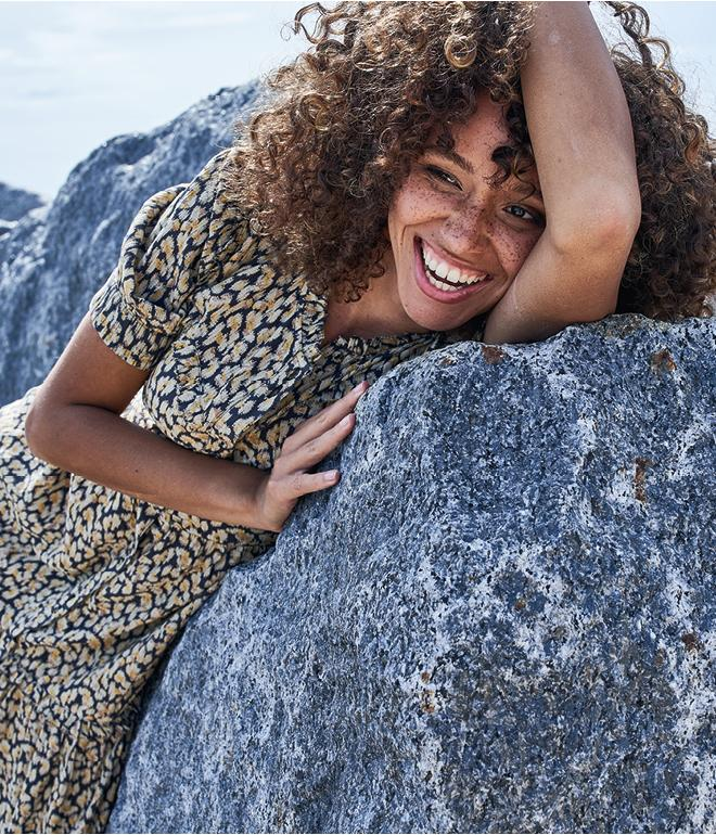 Woman leaning on a rock, wearing a yellow and black ditsy print midi dress.