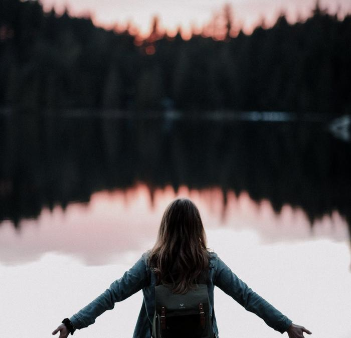 A girl holding her arms out to her sides whilst stood next to a lake in the forest.