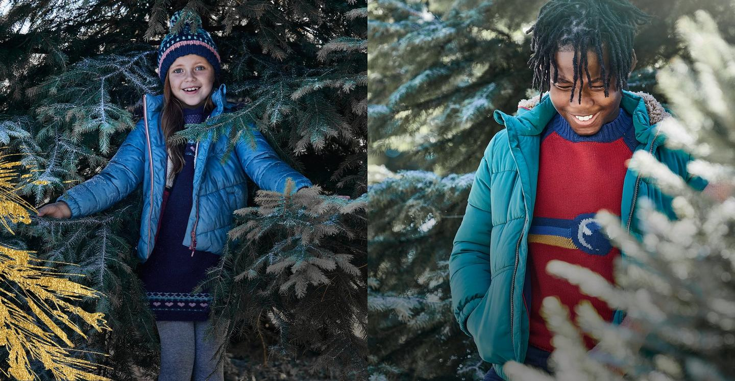 Girl wearing a blue puffer coat and fair isle dress next to a boy wearing a red jumper underneath a green puffer jacket.