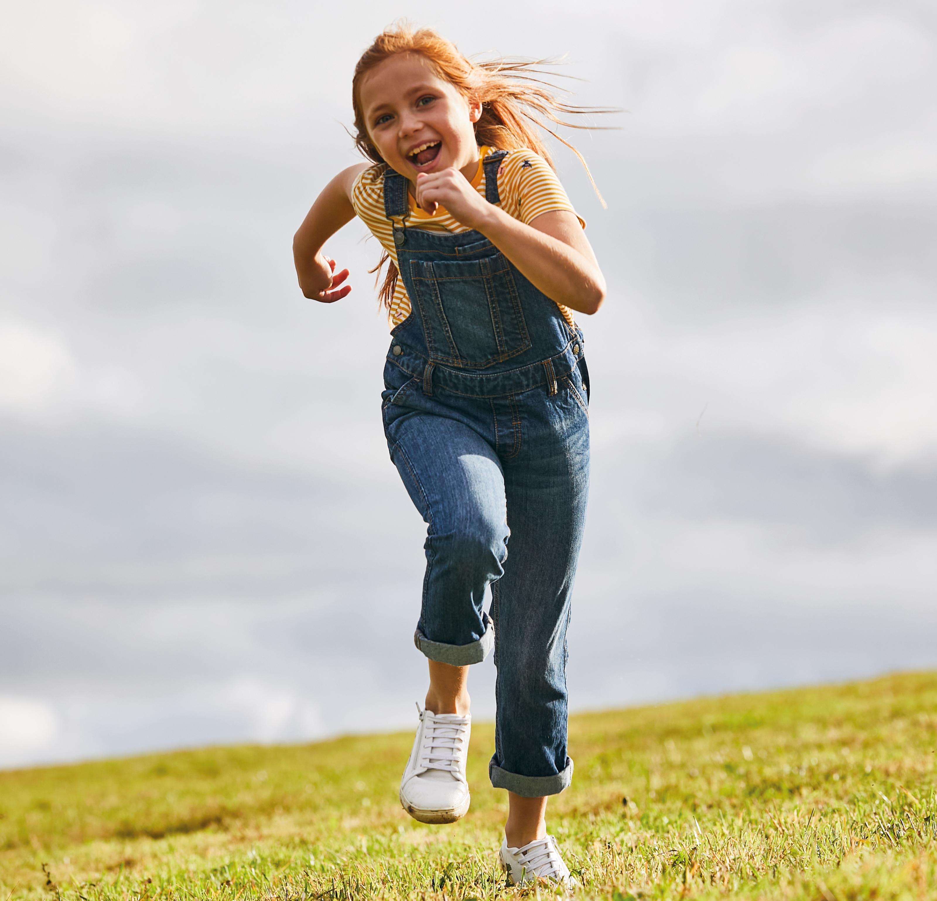 A girl on a hill wearing denim dungarees over a yellow & white striped T-shirt.