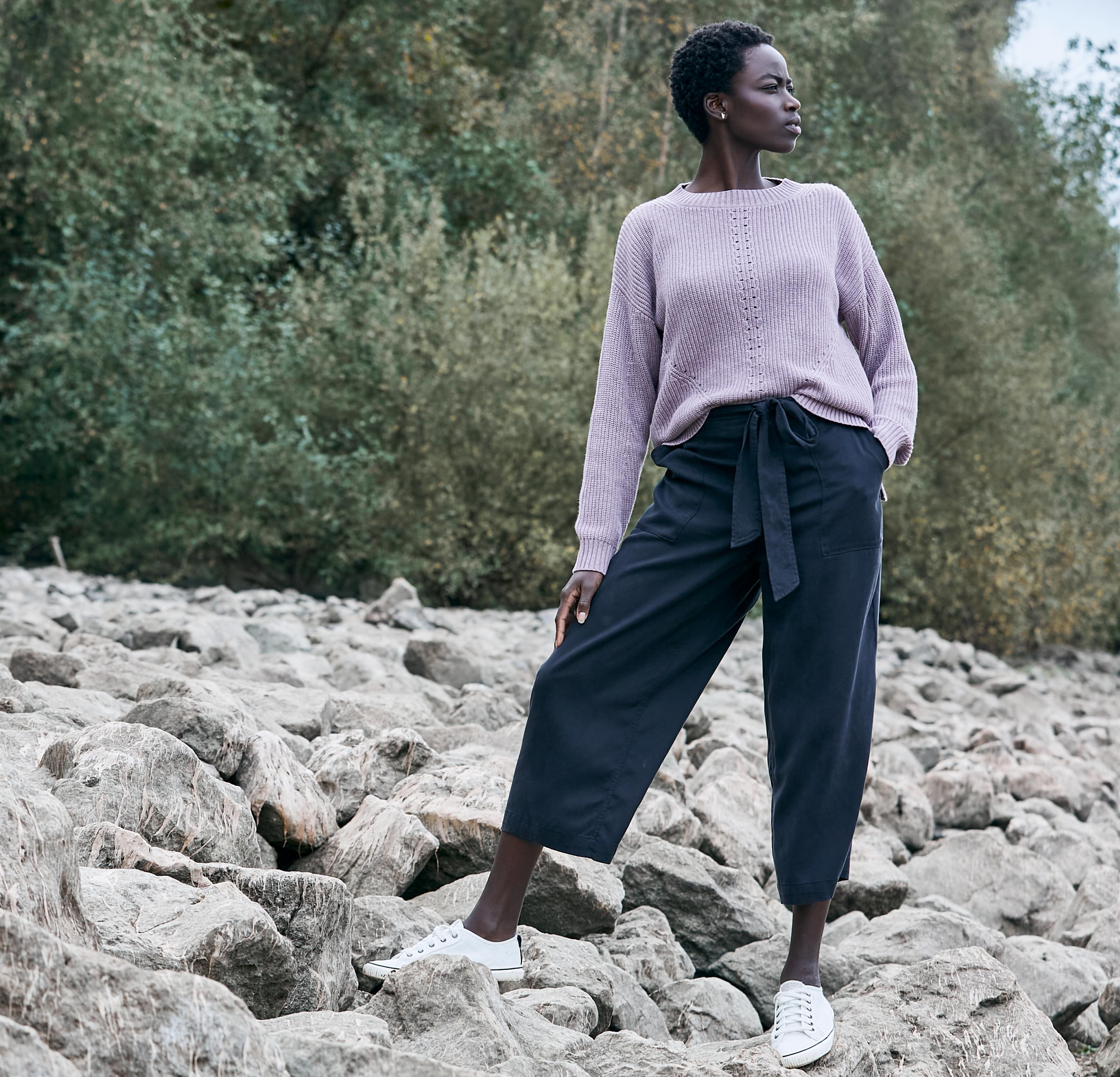 A woman standing on a rocky shoreline wearing a lilac jumper & navy cropped leg trousers.