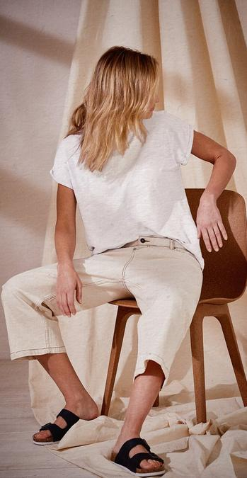 Female Fatface model wearing an ivory plain short sleeve t-shrit along with cropped trousers.