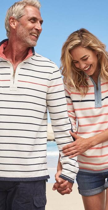 Man and woman FatFace model wearing striped Airlie Sweatshirts and walking on a beach.