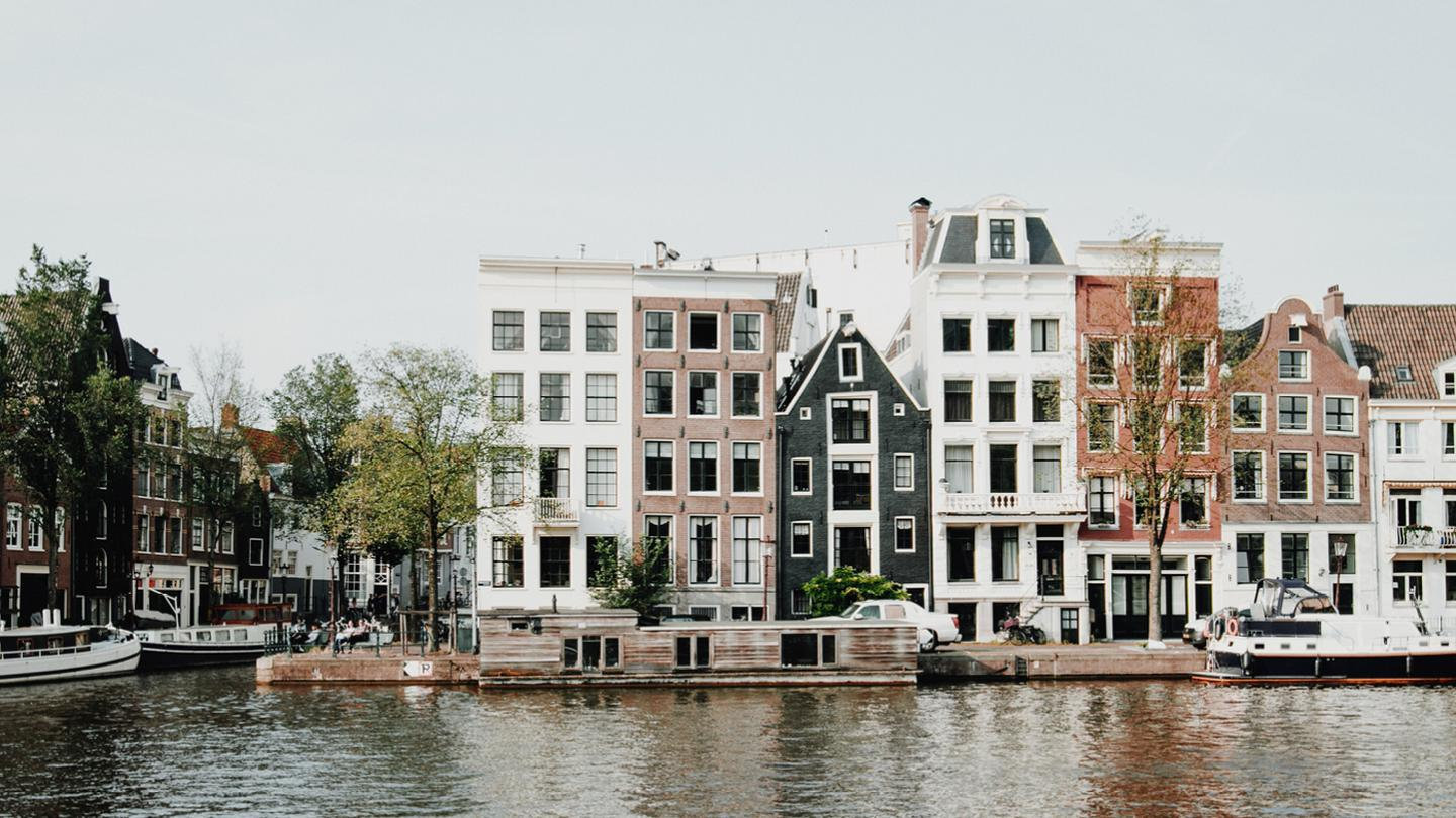 A beautiful street scene of Amsterdam next to a river