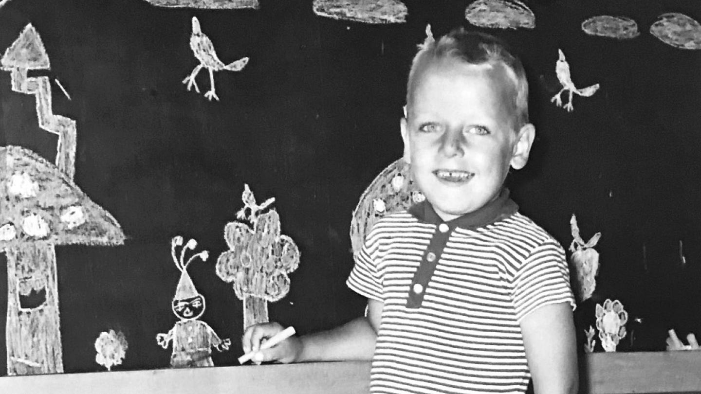 A four-year-old Peter, standing next to his drawing in the classroom