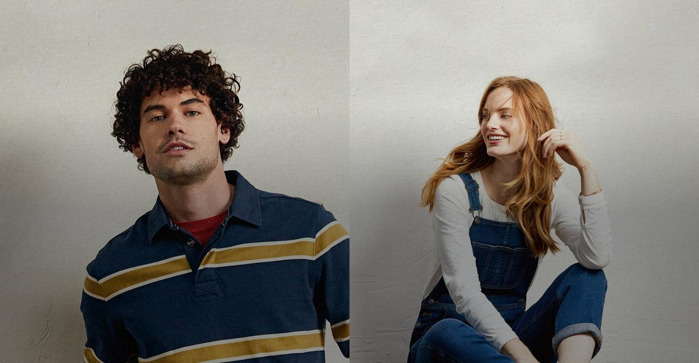 Male model wearing a blue and yellow striped rugby shirt, next to a female model wearing dark denim dungarees over a white t-shirt.