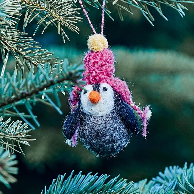 A knitted penguin decoration hanging in a Christmas tree.
