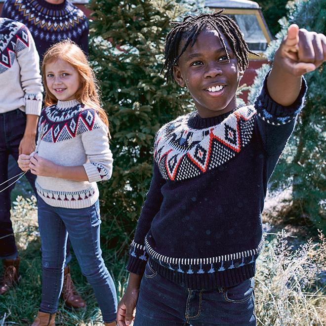 A girl and boy wearing coordinating navy red & white Fair Isle jumpers.