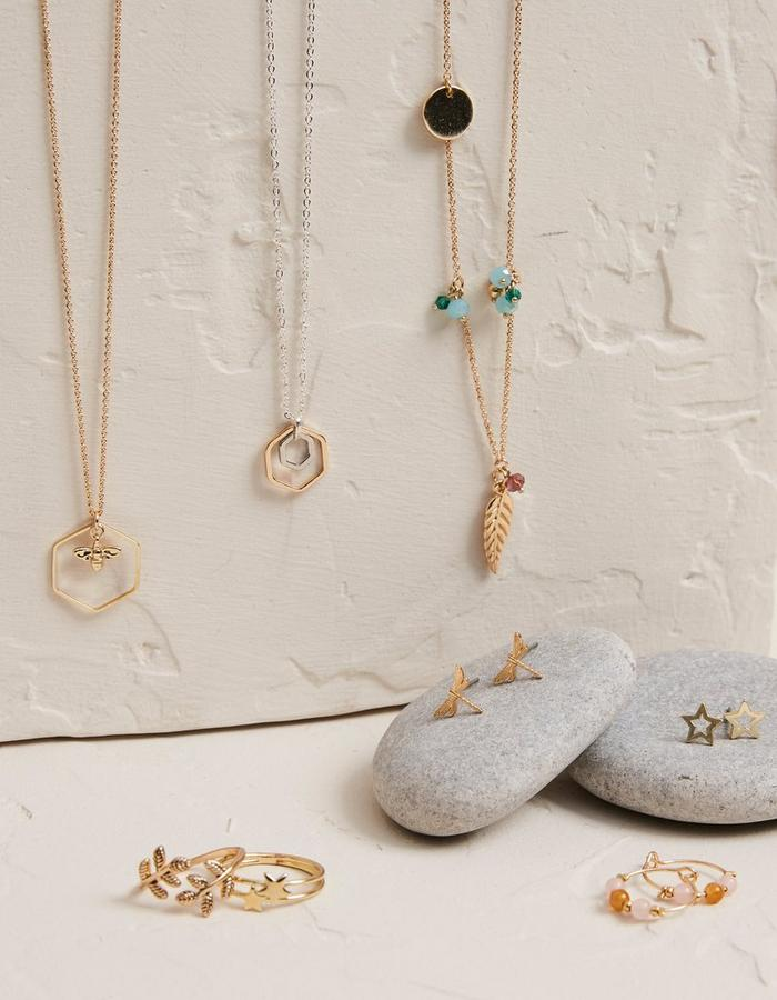 A selection of jewellery inspired by nature, including star rings, dragonfly earrings, and bee-themed necklaces.