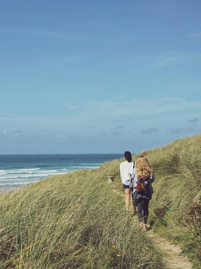 Two women walking along a grassy coastal path, beneath a blue sky.