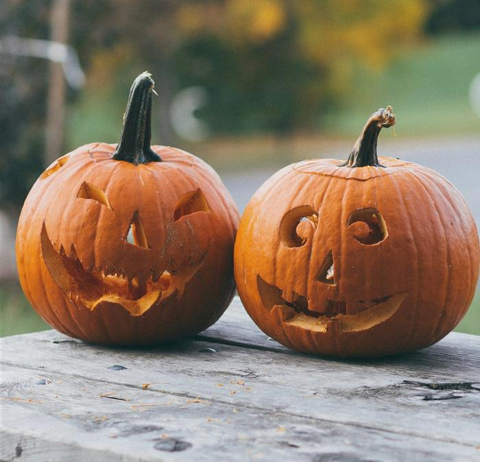 A pair of carved pumpkins sitting on a wooden table.