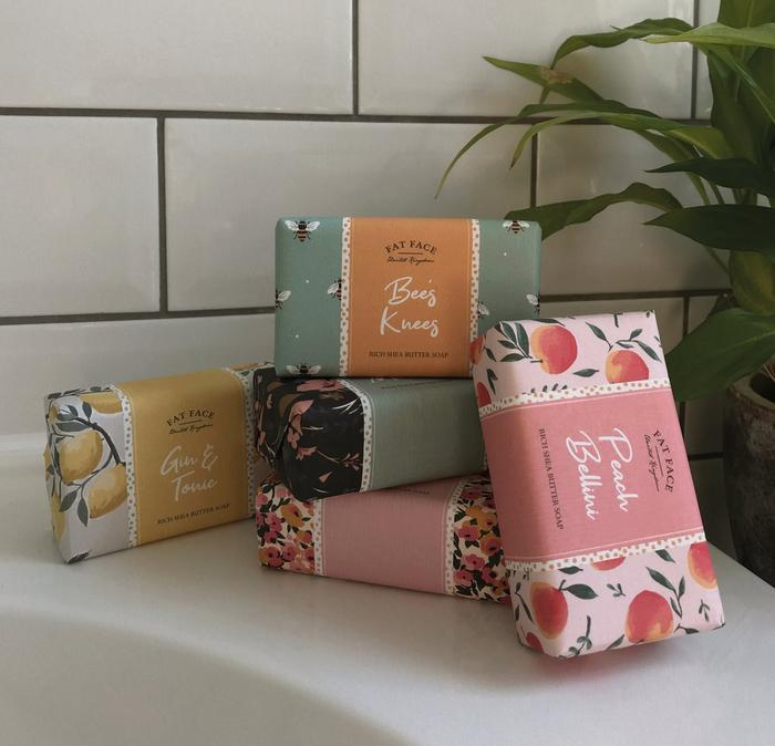 A selection of fruity and floral scented FatFace soaps displayed in front of white metro tiles.