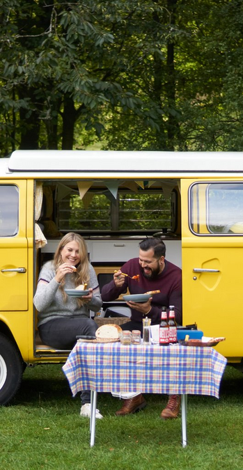 Two campers sitting in the door of their yellow campervan eating a hearty lunch.