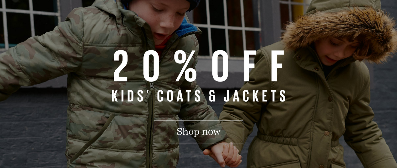 20% off kids coats and jackets. Shop now. In the background, a girl and boy playing outside, wearing warm coats.