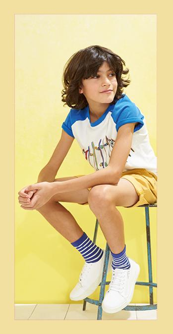 Boy sitting on a stool wearing a skateboard printed top with blue sleeves and yellow shorts.