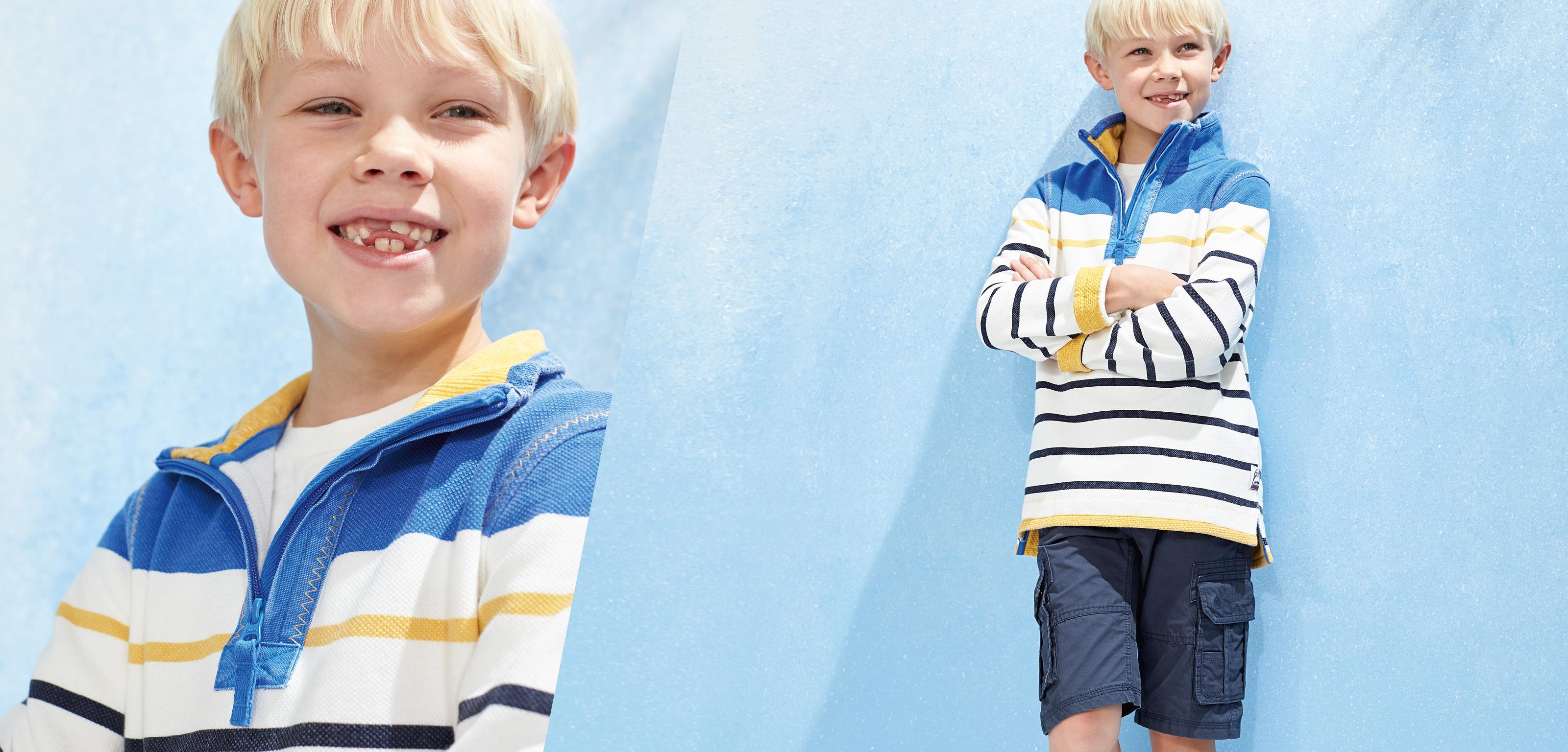 boy wearing stripey yellow and blue airlie sweat and blue shorts.