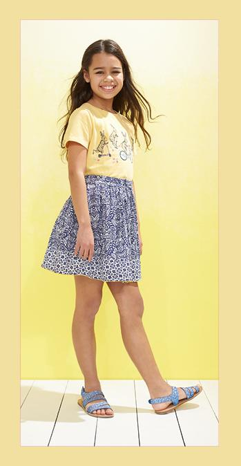Girl wearing a yellow printed top and patterned skirt with sandals.