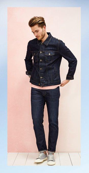 Male model wearing the Denim Western Jacket over the light shrimp Hawnby Organic Cotton Crew Tee with the denim Slim Rinse Jeans and the grey Organic Cotton Lace Up Trainers
