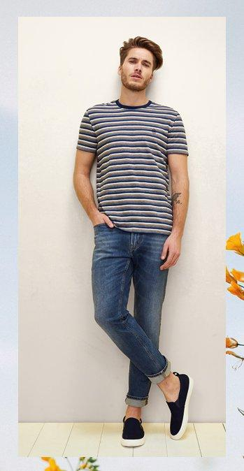Male model wearing the Telham Indigo Stripe Crew Tee with the denim Slim Mid Wash Jeans and navy Organic Cotton Slip on Trainers.
