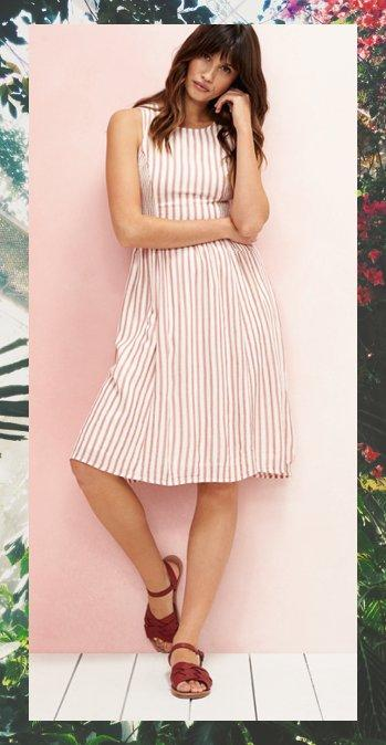 Female model wearing the Karen Stripe Dress on a pink background