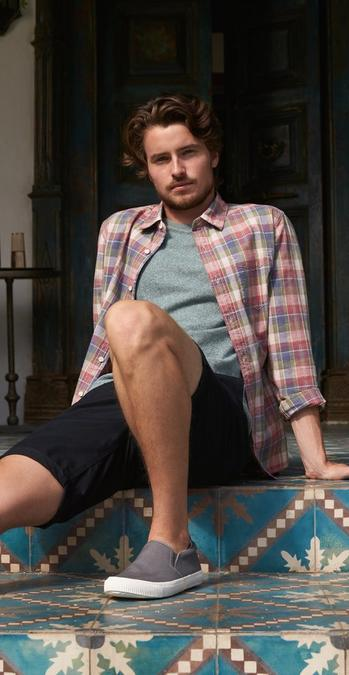 Male FatFace model wearing a check shirt and green t-shirt sat on a tiled moroccan floor.