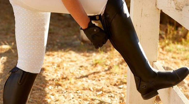 Woman putting on Ariat English riding boot
