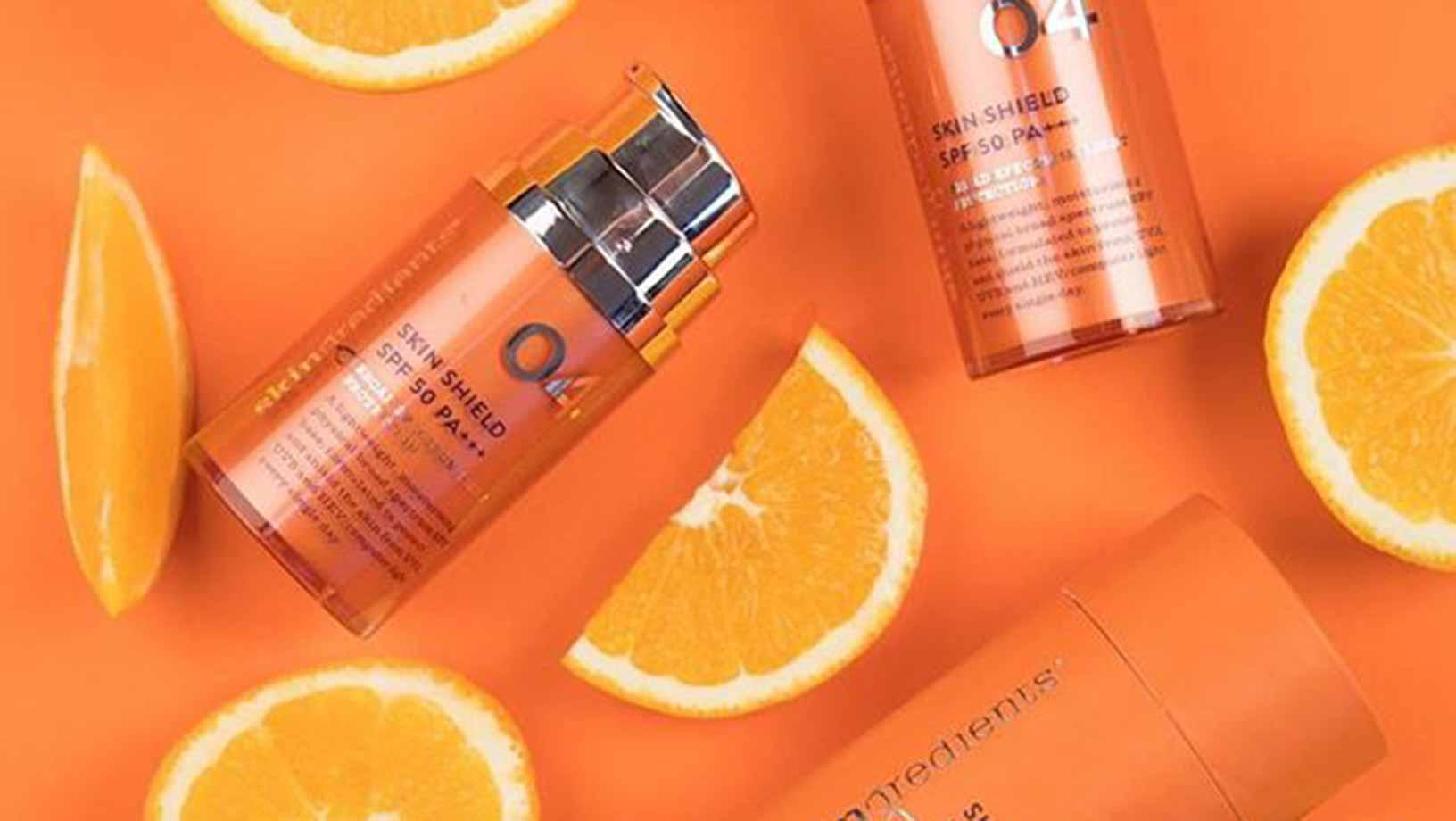 Skingredient Skin Shield SPF 50+++ on an orange background surrounded with orange segments