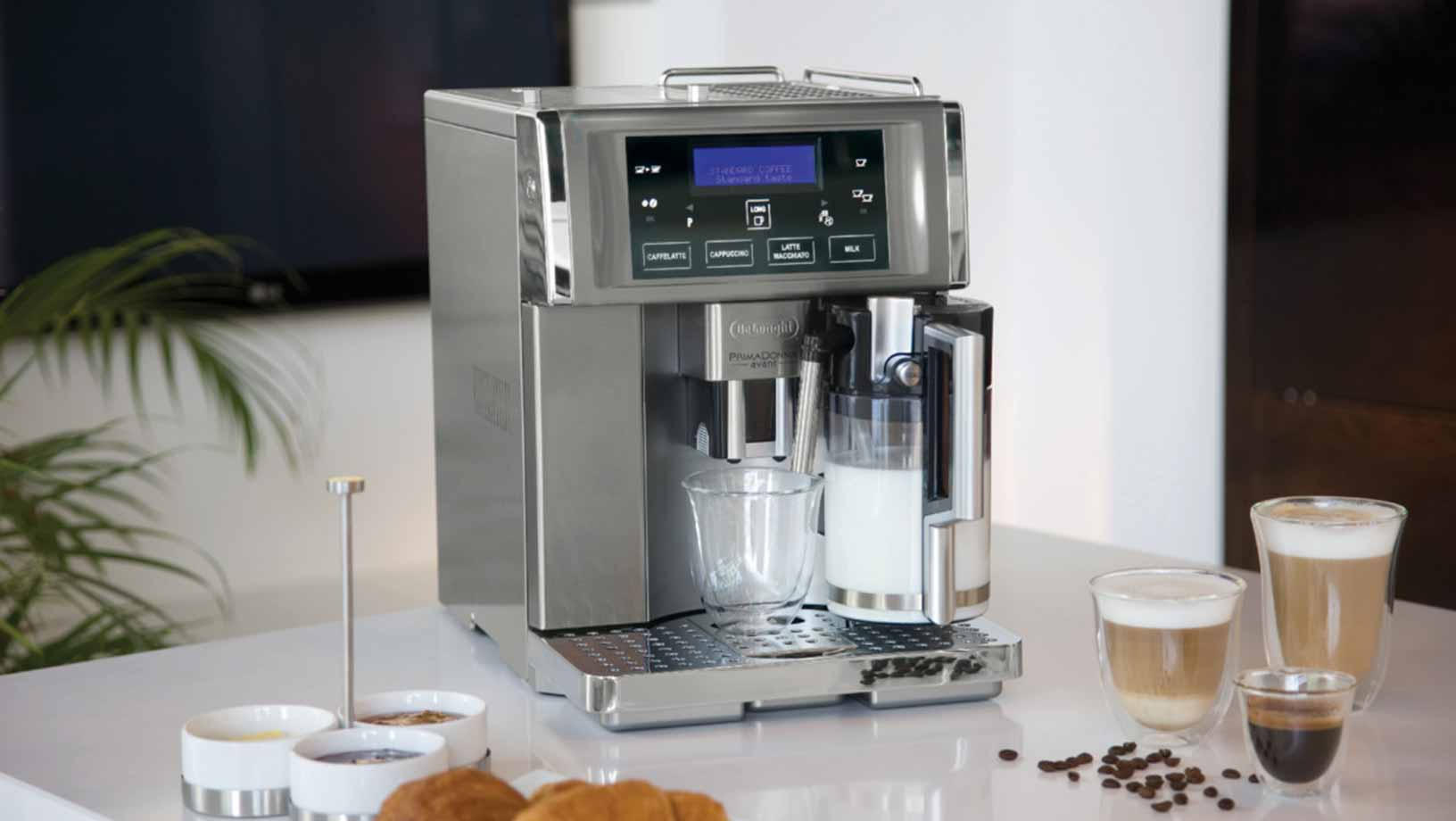 Silver coffee machine on a marbel counter top. Various cups of different types of coffee sit on the counter around it with some coffee beans spilt beside them.
