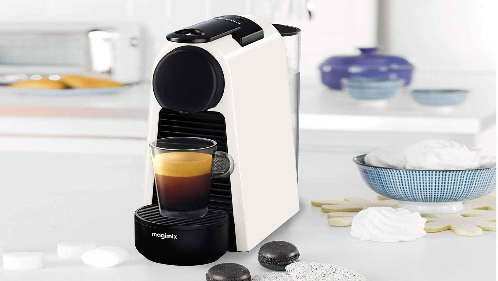 Black and white coffee maker sitting on a white bench in a bright kitchen. A coffee cup full of coffee sits in the machine and coffee pods sit on the counter beside the machine.