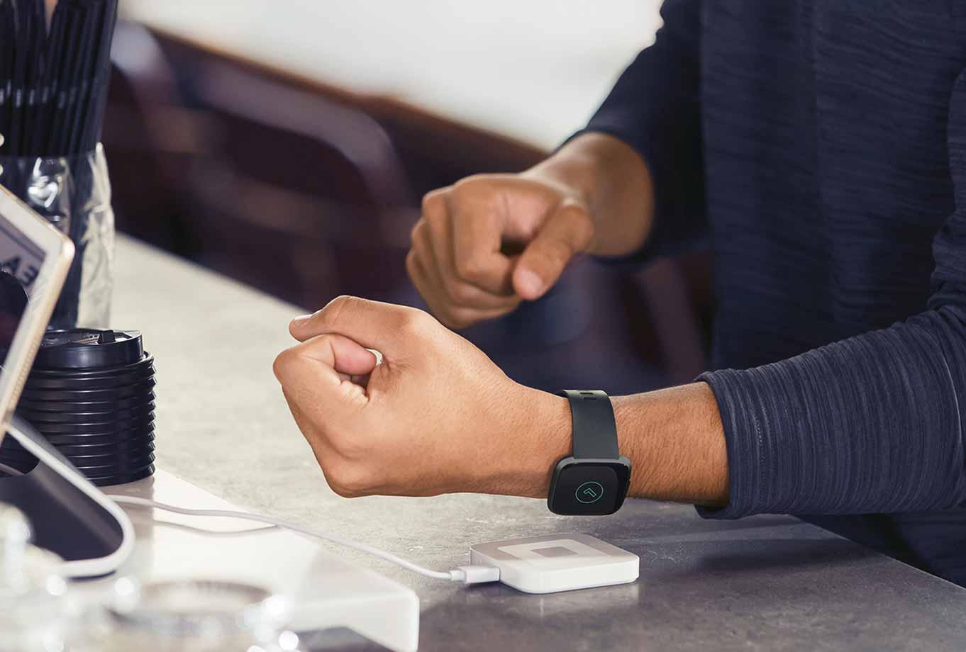 Aman wearing a black Fitbit watch is paying in a coffee shop using the watch and a tap device.